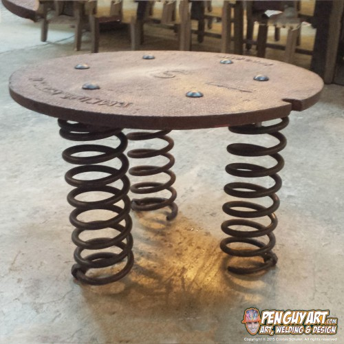 Costas_Schuler_Pen_Guy_Art_recycle_metal_art_manhole_cover_table_on_car_springs_03